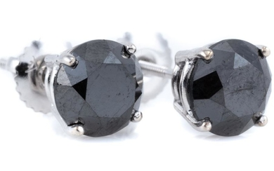 A PAIR OF SOLITAIRE BLACK DIAMOND STUD EARRINGS; each set with a round brilliant cut black diamond in 18ct white gold, diamonds tota...