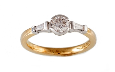 A SOLITAIRE DIAMOND RING, flanked by tapered baguette cut di...
