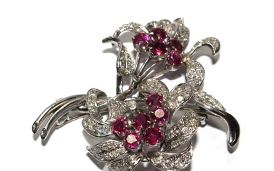 A diamond and ruby two headed flower brooch in fitted Carrin...