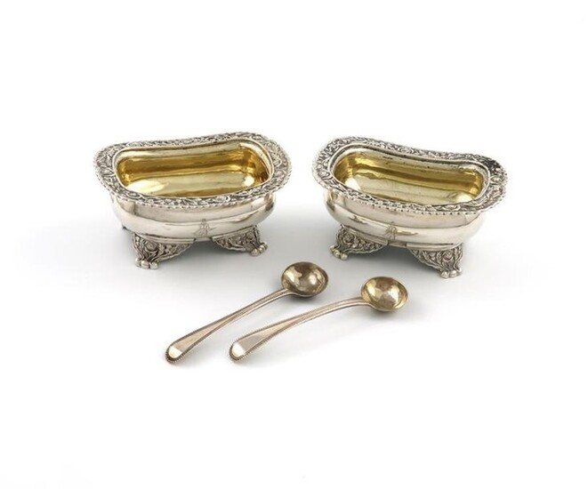 A pair of George IV silver salt cellars, by Charles and John Fry, London 1823, rounded rectangular form, foliate scroll borders, gilded bowls, on four foliate bracket feet, engraved with a crest, with two salt spoons, length 10.2cm, approx. weight...