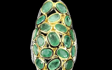 An emerald ring set with numerous oval-cut emeralds, mounted in rhodium and gold plated sterling silver. Size 56.