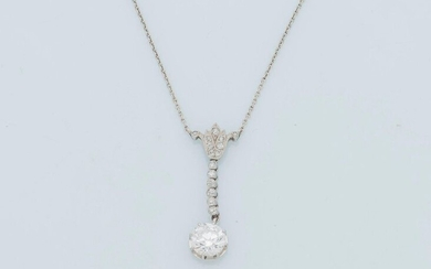 Platinum necklace (950 thousandths) composed of a fine chain supporting a lotus pattern paved with round old cut diamonds followed by a drop of diamonds in a closed setting ending with an old cut diamond of approximately 1.1 carat. Circa 1910.