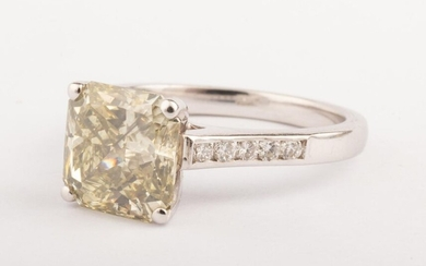 Ring in 18k white gold (750 thousandths) surmounted by a 2.64 ct. yellow diamond with a slight greyish tinge, radiant cut, SI2 quality. On the shoulders of the ring, two lines of five small round brilliant diamonds for about 0.30 ct. Very bright stone.