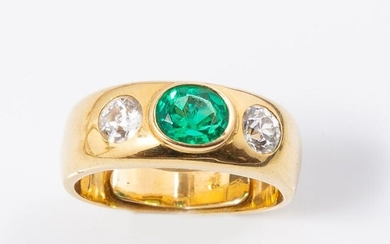 18k (750 thousandths) yellow gold rush ring set with an oval emerald of about 1 ct. of very beautiful colour and clarity, with natural multi-phase inclusions, surrounded by two round old cut diamonds of about 0.25 ct. each.