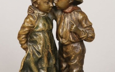 A COLD PAINTED BRONZE GROUP FIGURE OF A BOY WHISPERING TO A GIRL