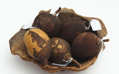 A COLLECTION OF FIVE CARVED BAOBAB NUTS WITH INCISED DECORATION BY ARTISTS INCLUDING JIMMY J, BOBBIE DAZZLER AND JABBI, TOGETHER WIT...