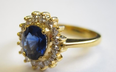A Sapphire and Diamond Cluster Ring claw-set oval-cut sapphire,...