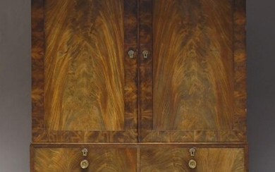A Victorian flame mahogany linen press, the moulded cornice above...