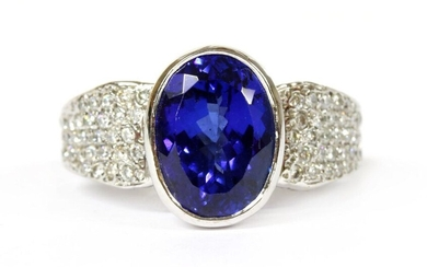 A white gold single stone tanzanite ring, an oval mixed cut tanzanite, with a stated weight of 6.31ct, rub set in a plain collet, to flat section tapering shoulders, micro pavé set with graduated brilliant cut diamonds to the shoulders, shank and...