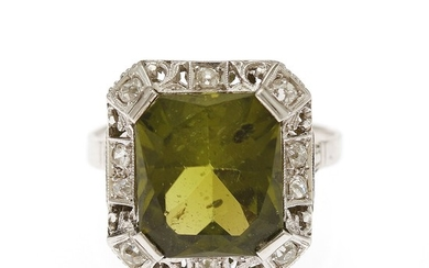 An Art Deco peridote and diamond ring set with a fancy-cut peridote encircled by numerous old-cut diamonds, mounted in platinum. Size 58.