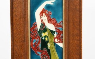 An Art Nouveau continental pottery plaque designed by Carl Sigmund Luber, probably manufactured by Johann Von Schwarz, slip decorated in low relief with a dancing maiden with long flowing red hair, glazed in colours, in oak frame 36 x 11.5cm (panel)...