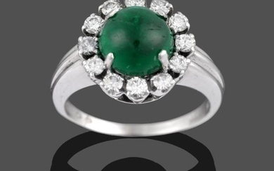An Emerald and Diamond Cluster Ring, the cabochon emerald within...