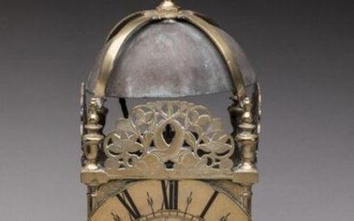 LANTERN CLOCK LANTERN in brass, topped by a spinning top supported by four others joined by a spacer above the bell. Each one rests on a Doric column. Three pediments decorated with dolphins with intersecting bodies surrounded by foliage and flowers...