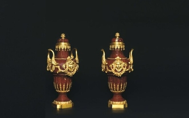 Pair of covered baluster-shaped vases in red marble, probably from Verona, decorated with a rich gilded bronze frame with a motif of female masks, with garlands of flowers held by the side handles ending with acanthus leaves. The neck is encircled by...