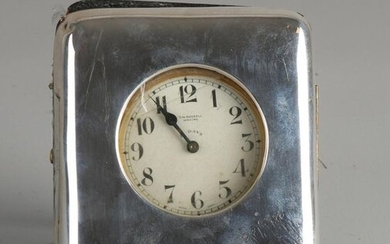 Travel watch in a holder with silver, 925/000. Yellow metal travel watch, TW Russell Woking in a leather case with a silver front with a monogram, worn. Glass of the watch is loose and the hinges of the holder are loose and somewhat dented. In...