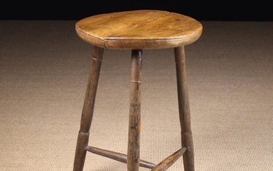 A 19th Century Cricket Table. The round twin plank top on three turned legs united by a turned T-fro
