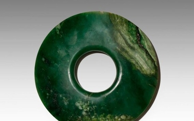 A CHINESE ARCHAISTIC SPINACH-GREEN JADE BI PROBABLY LATE QING DYNASTY The disc tapering at the edges, with a circular aperture to the centre, the dark green stone with pale and black inclusions, 18.4cm. Provenance: from a deceased estate, Hampshire.