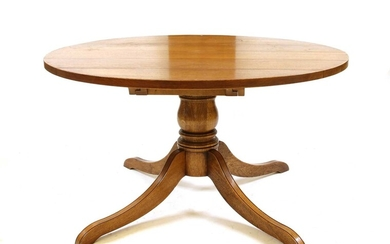 A modern solid oak extending pedestal dining table