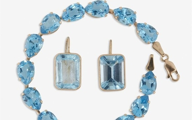 A pair of blue topaz and gold drop earrings...