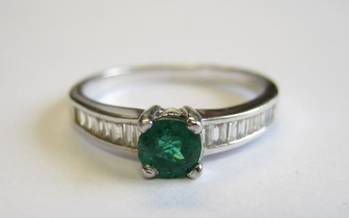 An Emerald and Diamond Ring claw-set round emerald between...
