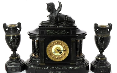 Black marble, green marble and patinated bronze Return from Egypt style mantel set, including a clock surmounted by a recumbent sphinx (H 44 x W 33 x D 15 cm) and a pair of vases (H 30 cm). Circa 1880 / 1900. Slight marble scratches. Functional...