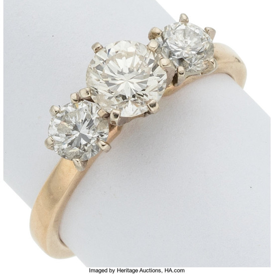 Diamond, Gold Ring The three-stone ring features a round...