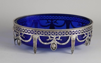 Silver jardiniere, 833/00, with blue glass inner container. Oval openwork dish decorated with garlands and medallions. Equipped with sawn and pearl edge. 2x broken at garland. jl .: presumably D: 1913. 25x18x8cm ;. In reasonably good condition