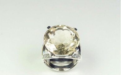 18K (750/oo) white gold ring centered on a large round smoky quartz set with four claws, the double ring decorated with lines of brilliant-cut diamonds. TDD 53. Gross weight: 11.5 g.