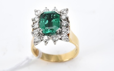 A SYNTHETIC EMERALD AND DIAMOND RING IN TWO TONE 18CT GOLD, DIAMONDS TOTALLING 0.53CTS, SIZE K