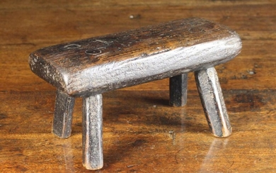 A Small Early 19th Century Rustic Stool. The thick oak plank seat inset with brass headed nails with