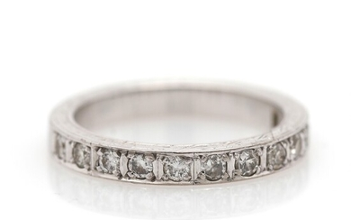 A diamond eternity ring set with numerous single and brilliant-cut diamonds, mounted in 14k white...