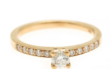 A diamond ring set with a diamond weighing app. 0.21 ct. flanked by ten diamonds, totalling app. 0.13 ct., mounted in 18k gold. Size 53.
