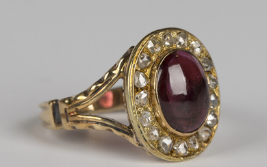 A gold, garnet and diamond oval cluster ring, collet set with an oval cabochon garnet within a surro