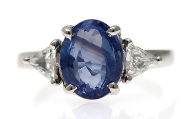 A sapphire and diamond ring set with an oval-cut sapphire weighing app. 3.65 ct. flanked...
