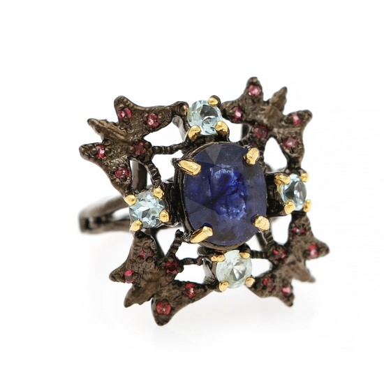 A sapphire, garnet and topaz ring set with an oval cut sapphire and numerous circular-cut garnets and topazes, mounted in gold- and black rhodium plated silver.