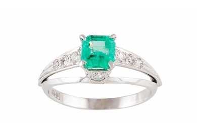 AN EMERALD AND DIAMOND DRESS RING, the trap cut emerald to d...