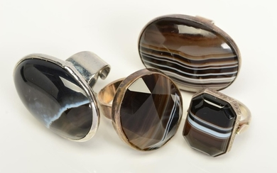 FOUR BANDED AGATE RINGS, two designed as oval banded agate c...