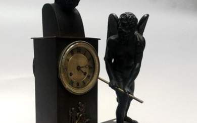 HANGING HANGER in brown patinated bronze, with a bust of a philosopher and the figure of Time on a terrace. The gilt bronze dial, with Roman numerals for the hours, is encircled with friezes of gadroons, lancets and pearls. Empire period. 46 x 31 x...