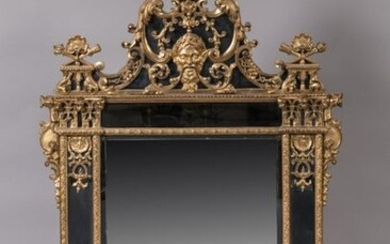 MIRROR with PARECLOSES in carved and gilded wood decorated with plant motifs, interlacing and shells, quivers and trophy flaming torches. In the upper part, a satyr mask with a laurel wreath has its moustache extended in interlacing. The framing...