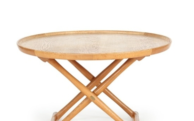 """Mogens Lassen: """"The Egyptian Table"""". Circular coffee table of patinated oak mounted on cross-legged, foldable frame with brass fittings."""