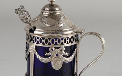 Silver mustard pot, 800/000, with blue glass inner pot. Mustard jar sawn with ovals and decorated with garlands with bows and medallions. Equipped with hinged lid with garlands. The jar is placed on 3 legs and has a blue glass inner tray. MT .:...