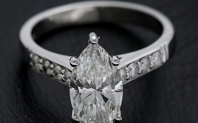 A diamond ring set with a marquise-cut diamond weighing app. 2.38 ct. flanked by numerous...