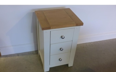 A painted three drawer bedside chest with an oak effect top,...