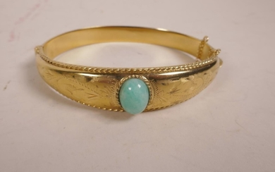 """A rolled gold bangle set with a green jade bead, 2½"""" wide"""