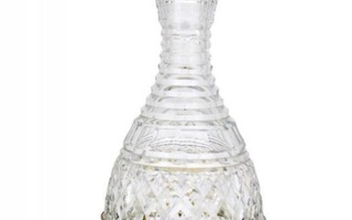 A rounded cut glass decanter raised on...