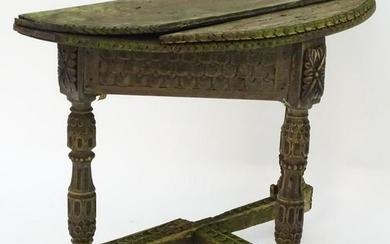 An antique credence table with a demi lune top and
