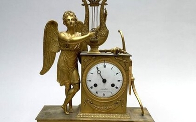 HANGING to pose in gilt bronze with a decoration of a Love playing the lyre, the white enamelled dial indicating the hours in Roman numerals signed Laurilliard rue du Faubourg St Honoré n°46 in Paris. Restoration period. 42.5 x 28.5 cm. Missing the...