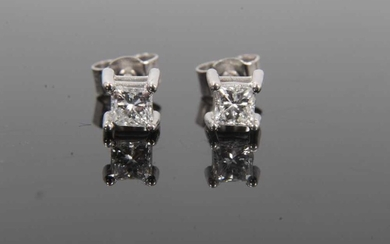 Pair of diamond single stone earrings, each with a princess cut diamond in 18ct white gold four claw setting, hallmarked London 2004. Estimated total diamond weight approximately 0.40cts