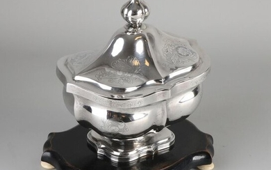 Silver tobacco jar, 833/000, on wooden base. Rectangular contoured tobacco jar with ribs and decorated with engraved elements and convex knob. MT .: W. Schutter, Groningen, yl.:L:1845. 18x14x23cm. Repaired at the base, otherwise in good condition