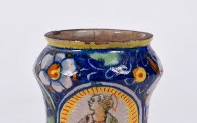 Small albarello in majolica decorated with flowers and fruits on a midnight blue background and a portrait of a saint in a medallion. France 16th century. H : 11 cm
